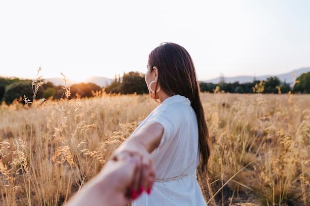 黄色のフィールドで夕暮れ時の屋外で若い美しい白人女性の肖像画。モダンな帽子をかぶって笑顔。手をつないで、概念に従ってください Premium写真