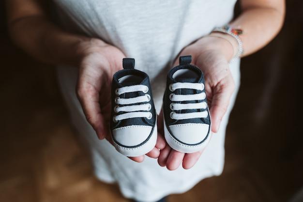 Молодая беременная женщина дома держит детскую обувь Premium Фотографии