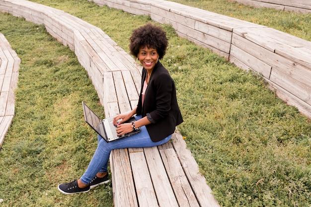 ラップトップを使用して、木製の階段に座って、笑顔の美しい若いアフロアメリカンの女性。ウッドの背景。アウトドアライフスタイル Premium写真