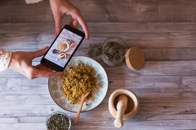 若い女性フードブロガーは、ブログ、木造モルタルの写真、黄色のウコン、ラベンダー、健康的な天然成分のボウルの写真を撮ります。セレクティブフォーカス、クローズアップ。昼間 Premium写真