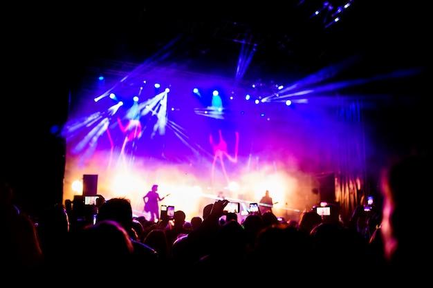 Изображение большого количества людей, наслаждающихся ночным выступлением, большой неузнаваемой толпой, танцующей с поднятыми вверх руками и мобильными телефонами на концерте. ночная жизнь Premium Фотографии
