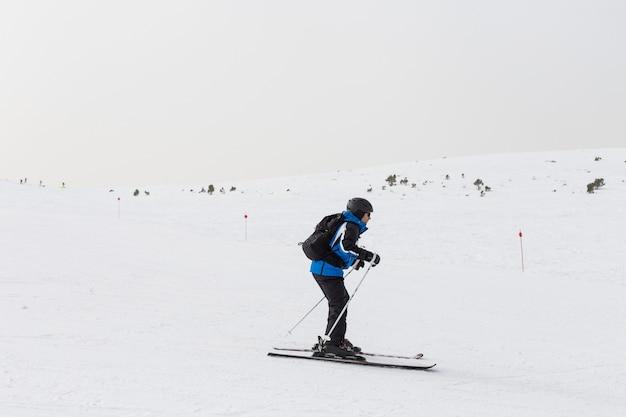 山の上にスキーヤーの男。冬季 Premium写真