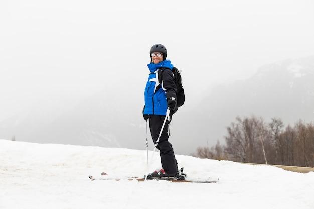 山の上にスキーヤーの男。霧。冬季 Premium写真