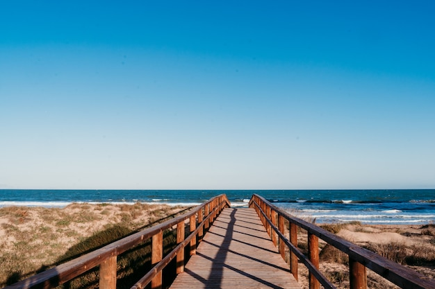 夕暮れ時の美しいビーチの風景。木製の橋の道。青空 Premium写真