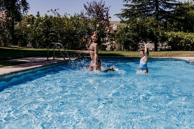 Две красивые сестры дети в бассейне играть, бегать и веселиться на открытом воздухе. летнее время и концепция образа жизни Premium Фотографии