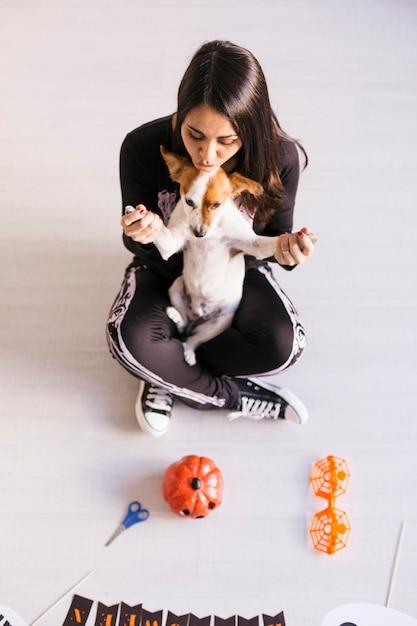 ハロウィンの準備をしているかわいい小さな犬を着た若い女性の平面図です。スケルトンの衣装を着ている女性。ハロウィーンのコンセプト。屋内で Premium写真