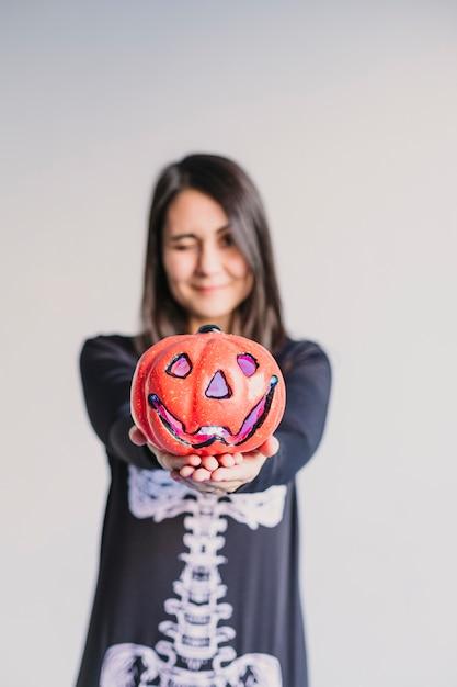 カボチャを押しながらウインク顔を作る若い女性。黒と白のスケルトンコスチュームを着ています。ハロウィーンのコンセプト。屋内。ライフスタイル Premium写真