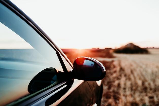 フィールドの夕暮れ時の車とリアミラーのビューを閉じます。旅行のコンセプト Premium写真