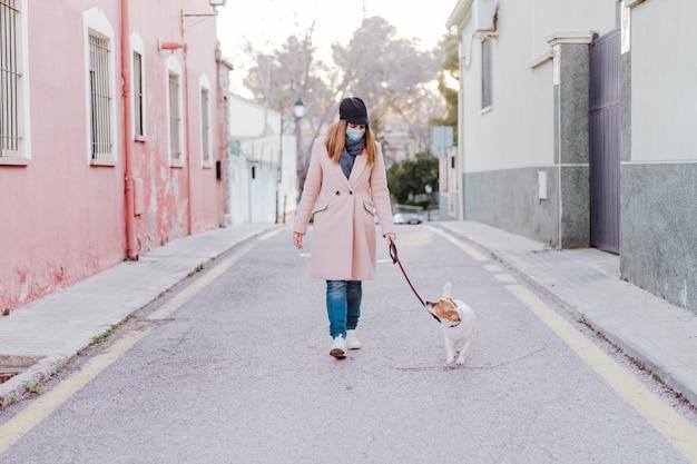 防護マスクを着用し、彼女の犬を連れて歩いて通りの白人女性 Premium写真