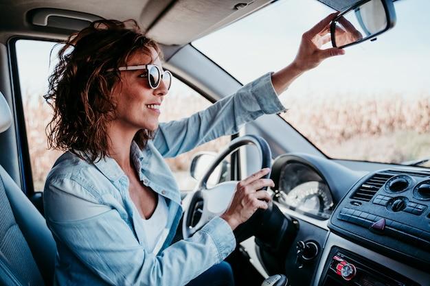 車を運転して、リアミラーを調整する若い美しい女性。旅行の概念 Premium写真