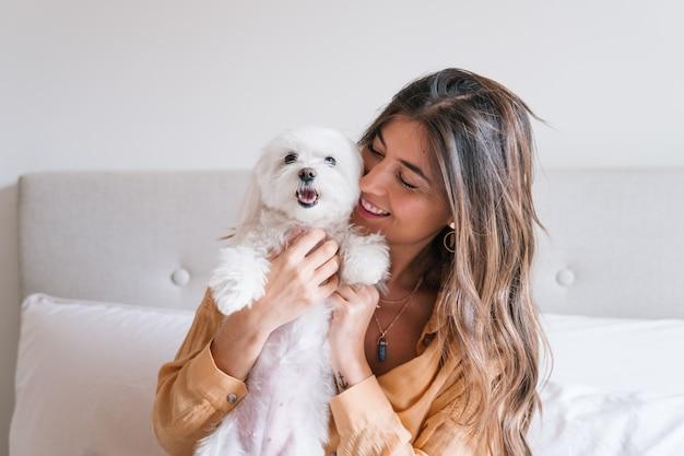 Женщина играет со своей собакой дома Premium Фотографии