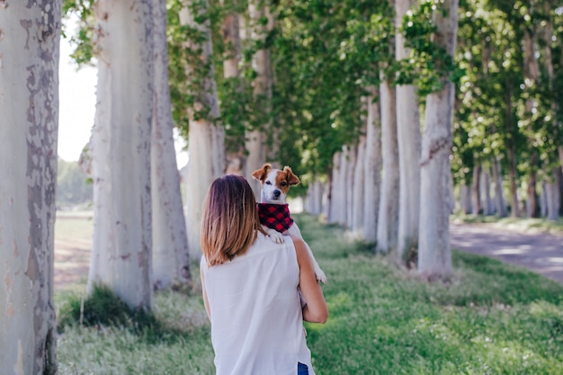 Молодая красивая женщина, держа ее милая маленькая собака на плече. на открытом воздухе. любовь к животным концепции и образ жизни на открытом воздухе Premium Фотографии