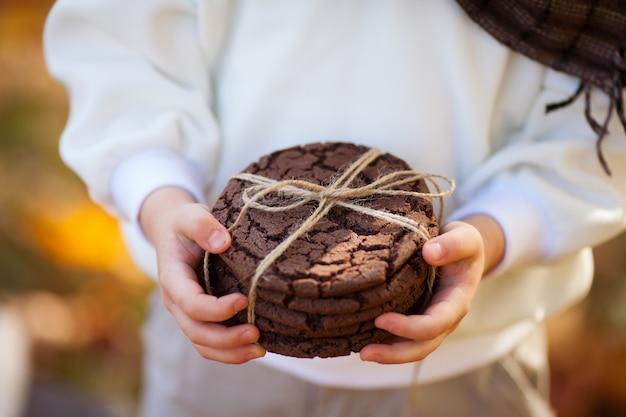 Ребенок, держащий овсяное печенье в руках. закройте вверх по фото очень вкусных и хрустящих печений овсяной каши на предпосылке осени. выпечки складывают в ряд друг на друга и обвязывают натуральной тесьмой. Premium Фотографии
