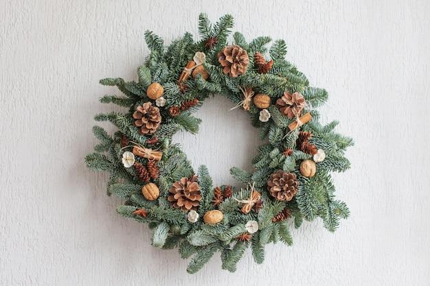 白い壁に掛かっている自然なモミの枝で作られたクリスマスリース。 Premium写真