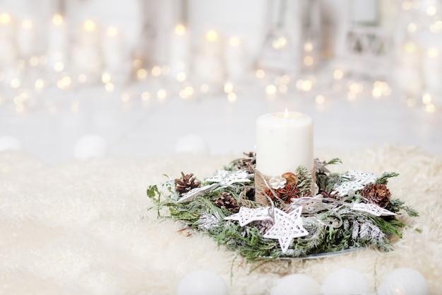 Рождественские свечи и снежные ели ветви на белом фоне с огнями. новогоднее украшение с елкой в белых тонах. Premium Фотографии