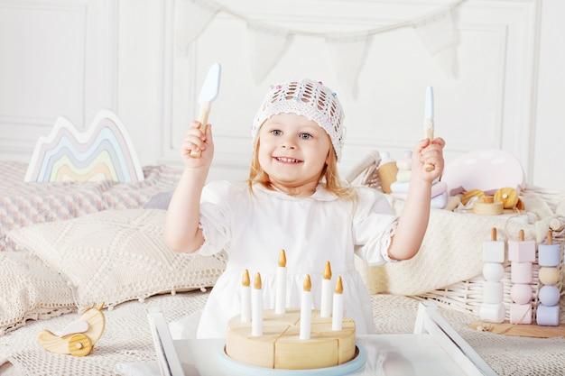 Детская девочка, играющая с деревянным игрушечным пирогом. Premium Фотографии