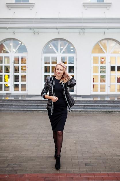 Счастливый красивая женщина, развлекаясь на улице города. мода женщина идет по улице на высоких каблуках. Premium Фотографии