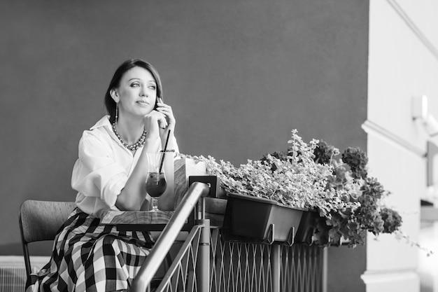 テーブルに座って電話で話している素敵な思いやりのある若い女性。フレッシュジュースとテーブルの上のノートパソコンのガラス。市内のストリートカフェ。黒と白の画像。コピースペース Premium写真