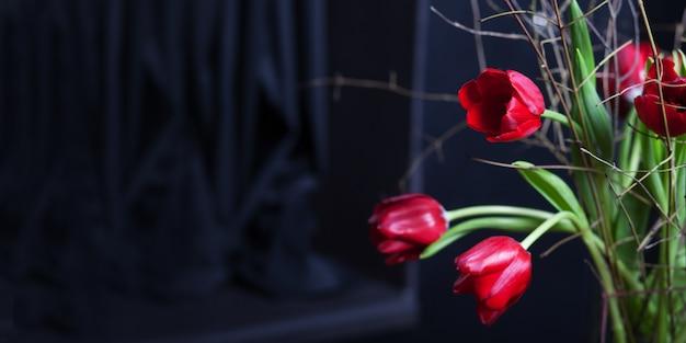 黒い背景にガラスの花瓶に美しいチューリップの花赤い色。バレンタインデーや母の日グリーティングカード。テキストのスペースをコピーします。バナー Premium写真