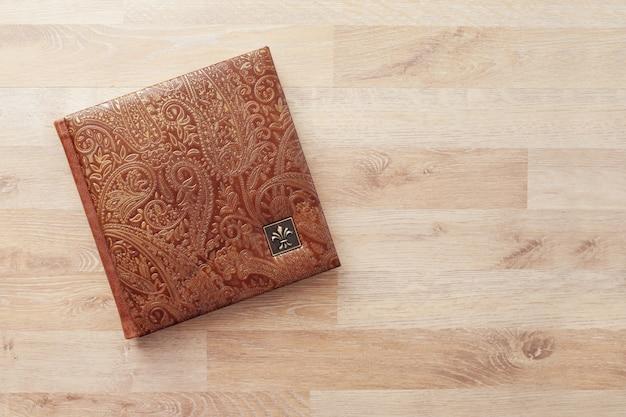 本革のカバーが付いている写真集、ノートまたは日記。装飾的なスタンピングを施した茶色の色。結婚式や家族の写真アルバム。コピースペース。 Premium写真