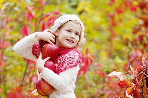 秋の庭でリンゴを保持している美しい少女。 。リンゴの木の果樹園で遊ぶ少女。秋の収穫で果物を食べる幼児。子供のための屋外の楽しみ。健康的な栄養 Premium写真