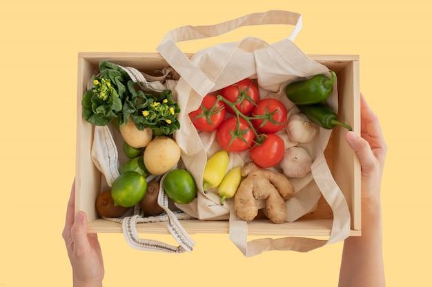 Вручите владению коробку сосны деревянную и мешок хлопка чистый с положением квартиры свежих овощей на желтой предпосылке без пластика для покупки продуктов и доставки. безотходный образ жизни Premium Фотографии