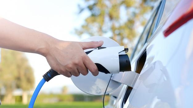 На станции заряжается электромобиль или эв. человек использует белый кабель питания и вилку Premium Фотографии