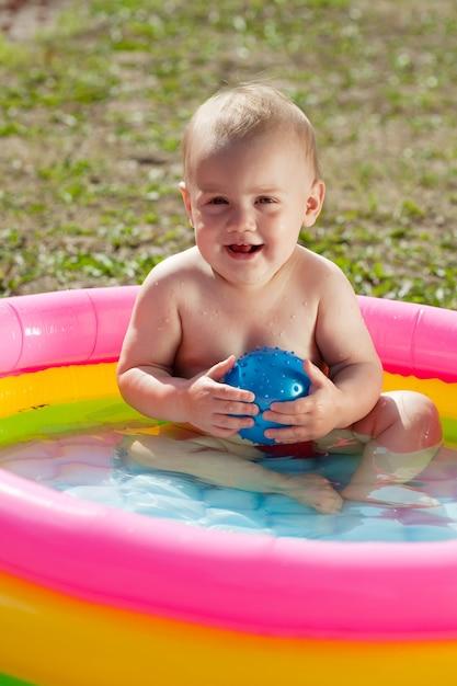 Счастливый ребенок плавает в надувном бассейне Бесплатные Фотографии