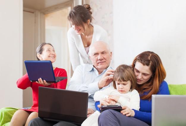 Семья с несколькими поколениями использует несколько портативных электронных устройств Бесплатные Фотографии