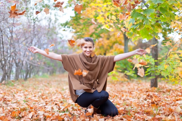 女は秋の葉を投げる 無料写真
