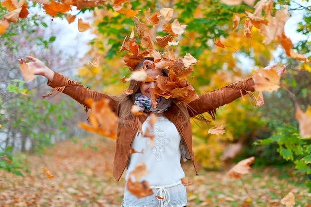 幸せな女性が秋の葉を投げる 無料写真