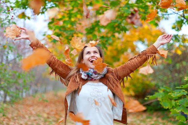 幸せな女性が葉を投げる 無料写真