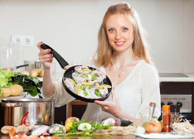 レモンで魚を料理する笑顔の女の子 無料写真