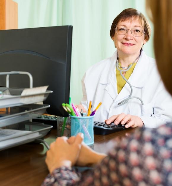 女性の医者と女性が何かを話し合う 無料写真