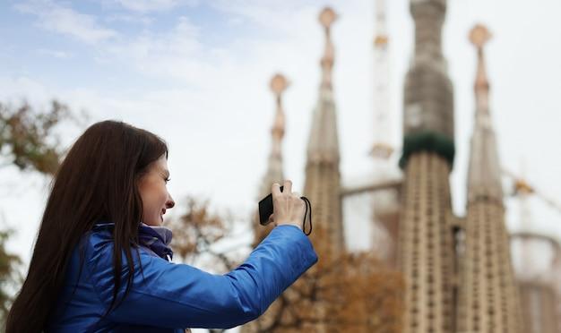 バルセロナでサグラダ・ファミリアを撮影している女性観光客 無料写真