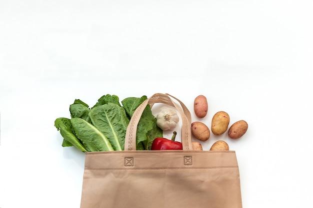 無駄のないプラスチックの使用エコテーブルコットン生地の袋に入れた新鮮な野菜を木製のテーブルに入れる Premium写真