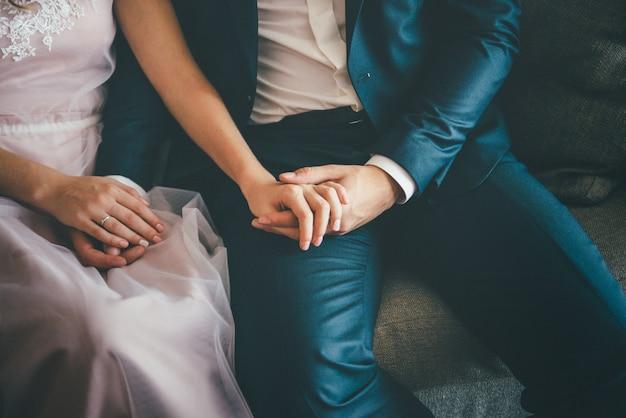 エレガントな新郎と新婦が座っています。手をつないで、クローズアップ Premium写真