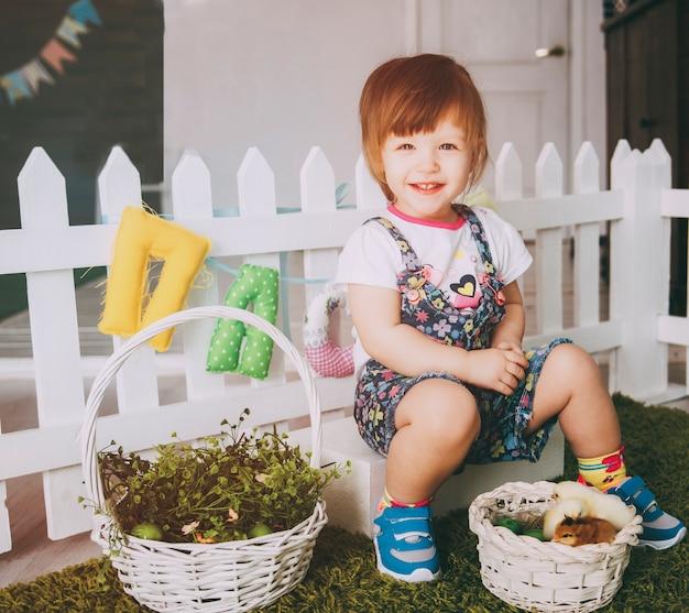 Маленькая девочка играет с курицей на ковре Premium Фотографии