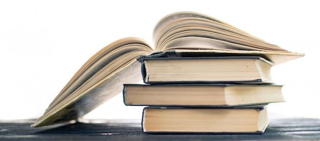 珍しい本の山。開いた本、木製のテーブルのハードカバーの本。 Premium写真