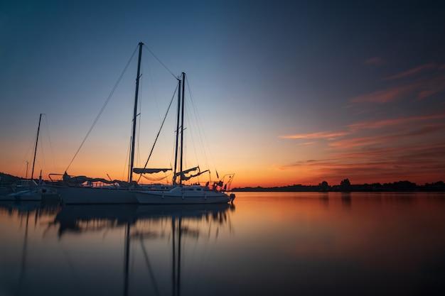 休日休暇旅行の概念:休日休暇日没日の出帆岸壁のヨット。航海、リラクゼーション Premium写真