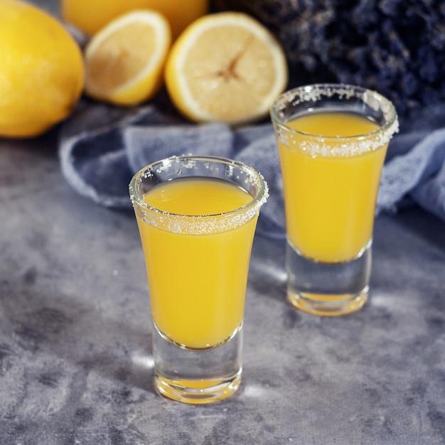 黄色の新鮮なショットカクテルまたはレモンとレモネード Premium写真