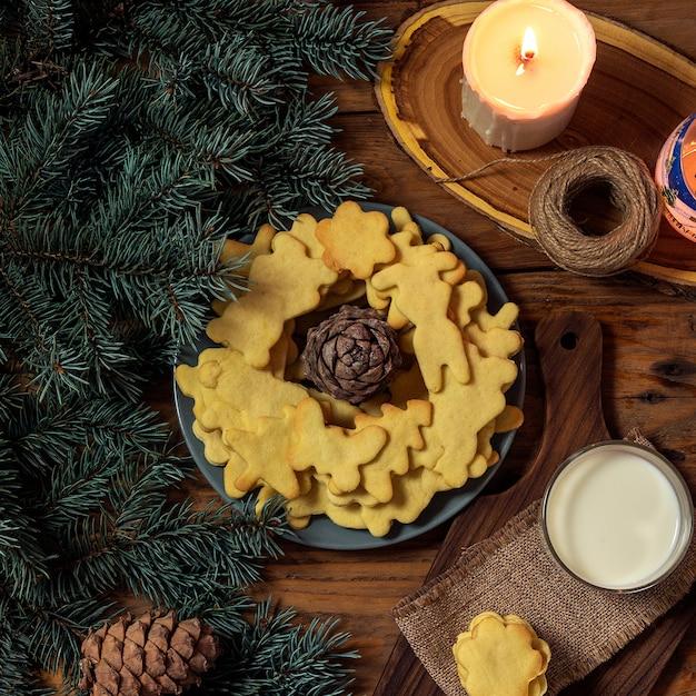 おいしいクリスマスクッキー、キャンドル、木製のテーブルのギフトプレート。上面図。 。 Premium写真