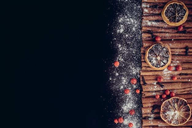 Рождественская пекарня и новогоднее понятие. праздник фон с ломтиками лимона цитрусовых, набор палочек корицы и ванильного порошка. уютный зимний праздник выпечки, глинтвейн винная рамка на темном фоне. Premium Фотографии