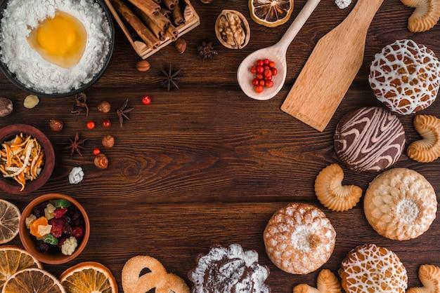 クリスマスベーカリーコンセプトの背景。ベーカリーセットと居心地の良い静物:自家製クッキー、ケーキ、ナッツ、シナモン、フレーバー、卵クランベリー、レモン、暗い木製のテクスチャの乾燥柑橘類。 Premium写真