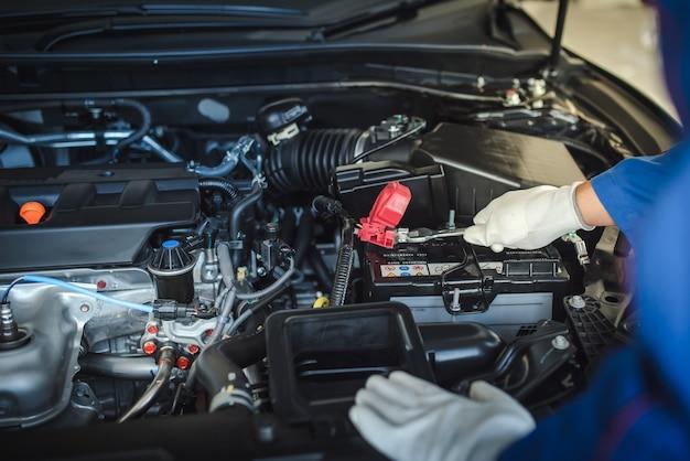 制服を着たハンサムなメカニックのトリミングされた画像は、自動車サービスで働いています。車の修理とメンテナンス。 Premium写真