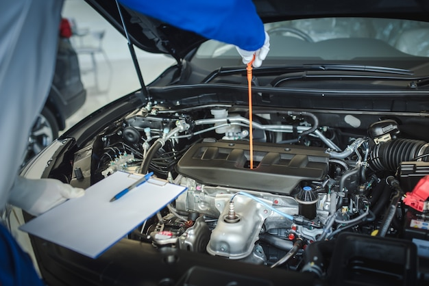 自動車整備士がオイルレベルゲージを引き上げて、オイルレベルを確認しています。車の状態を確認するには Premium写真