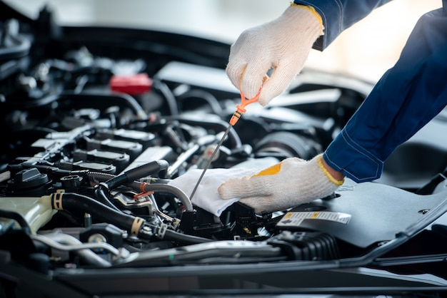 Азиатский автомеханик в ремонтной мастерской проверяет двигатель. для клиентов, которые используют автомобили для ремонта, механик будет работать в гараже. Premium Фотографии