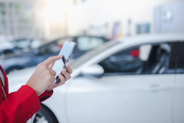 車のセールスマンアジアの女性がスマートフォンを保持 Premium写真
