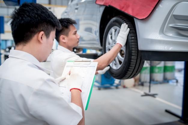 技術者が車両の検査を行い、車両の所有者のためにメモを取ります Premium写真
