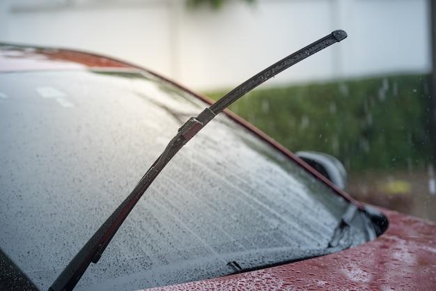 雨季に雨の中で駐車し、フロントガラスからフロントガラスを取り除くワイパーシステムを備えた車 Premium写真